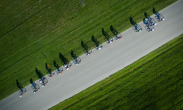 Shadows of cyclists chase each other along a straightaway during the Men's Masters 40+ race of the Tour of Lawrence Haskell Campus Criterium at Haskell Indian Nations University on Saturday, July 16, 2016.