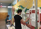 Vincent Weston, of Lawrence, adds detail to a mural he helped design with his mother, art teacher Julia Rose-Weston, inside New York Elementary School, 936 New York St., on Thursday, June 21, 2018. Rose-Weston, the mural's lead designer, has been aided by at least 20 volunteers over the last few weeks, including Lawrence High School student Katie Grear, pictured here in the background.