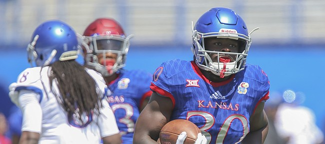 Kansas running back Kezelee Flomo (30) makes his way up the field after a catch during an open practice on Saturday, April 28, 2018 at Memorial Stadium.