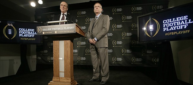 FILE — Bowl Championship Series executive director Bill Hancock, left, and former Arkansas athletic director Jeff Long, chairman of the College Football Playoff Committee, announce the 12 members selected to the committee during a news conference, Wednesday, Oct. 16, 2013, in Irving, Texas. The University of Kansas announced Long as its new athletic director on July 5, 2018. (AP Photo/Tony Gutierrez)
