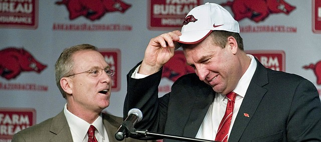 In this Dec. 5, 2012, file photo, Arkansas athletic director Jeff Long, left, presents Bret Bielema with a cap as Bielema is introduced as the school's new head coach during an NCAA college football news conference in Fayetteville, Ark. Kansas named Long its new A.D. on July 5, 2018.  (AP Photo/April L. Brown, File)