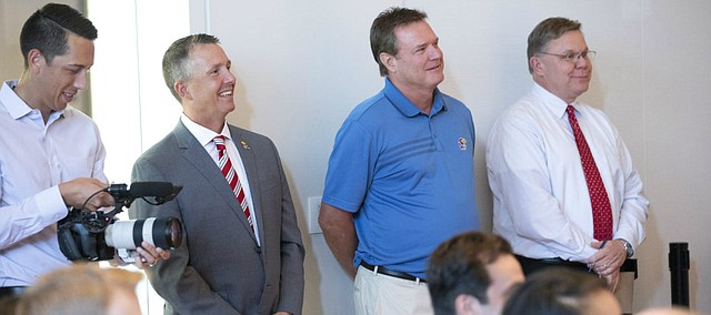 Kansas head basketball coach smiles next to assistant athletic director Sean Lester as new University of Kansas athletic director Jeff Long speaks to those gathered for his introductory news conference on Wednesday, July 11, 2018 at the Lied Center Pavilion.