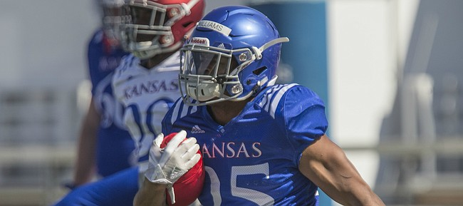 Kansas sophomore running back Dom Williams (25) runs through warmups on Monday, April 23, 2018.