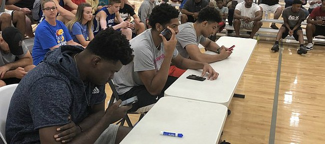 Current Jayhawks, from left to right, Udoka Azubuike, Dedric Lawson and Quentin Grimes showed up at Sports Pavilion Lawrence on Friday night and chipped in at the Hardwood Classic by judging the 2018 slam dunk contest. KU sophomore Marcus Garrett also helped hand out scores.