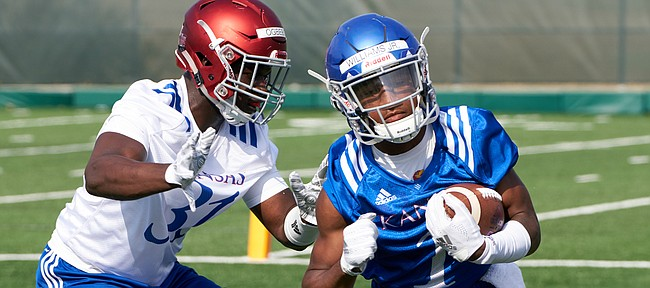 Kansas freshman running back Pooka Williams scoots past senior linebacker Osaze Ogbebor during practice drills on Aug. 4, 2018