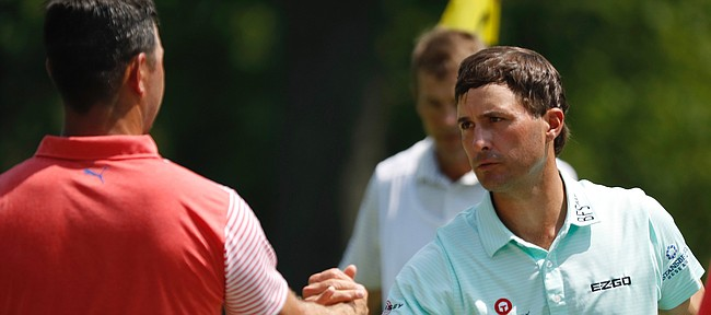 Gary Woodland, left, shakes hands with Kevin Kisner, right, on the ninth green after they finished the second round of the PGA Championship golf tournament at Bellerive Country Club, Friday, Aug. 10, 2018, in St. Louis. (AP Photo/Brynn Anderson)