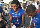 University of Kansas football players Corione Harris (No. 2) and Pooka Williams (No. 1) sign autographs for fans at the KU Kickoff event in Prairie Village, on Aug. 17, 2018.