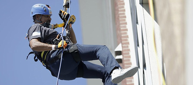 Kansas men's basketball assistant coach Kurtis Townsend rappels down the 888 Lofts, 888 New Hampshire St., in the Over the Edge fundraising event for Boys & Girls Club of Lawrence, Saturday, Aug. 25, 2018.