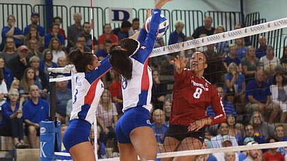 Juniors Patricia Montero (left), and Zoe Hill block a ball from Arkansas sophomore Elizabeth Pamphile. Kansas fell to Arkansas Sunday afternoon in four sets.