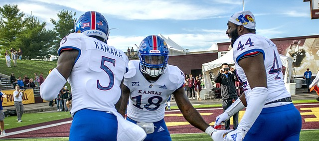 Kansas redshirt junior linebacker Denzel Feaster (18) high-fives junior defensive end Azur Kamara (5) and redshirt junior defensive end Willie McCaleb (44) as they leave the field following the team's 31-7 win over Central Michigan, the program's first road win since 2009.