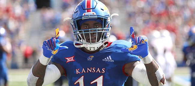 Kansas safety Mike Lee (11) celebrates before the cameras after returning an interception for a touchdown during the second quarter on Saturday, Sept. 15, 2018 at Memorial Stadium.