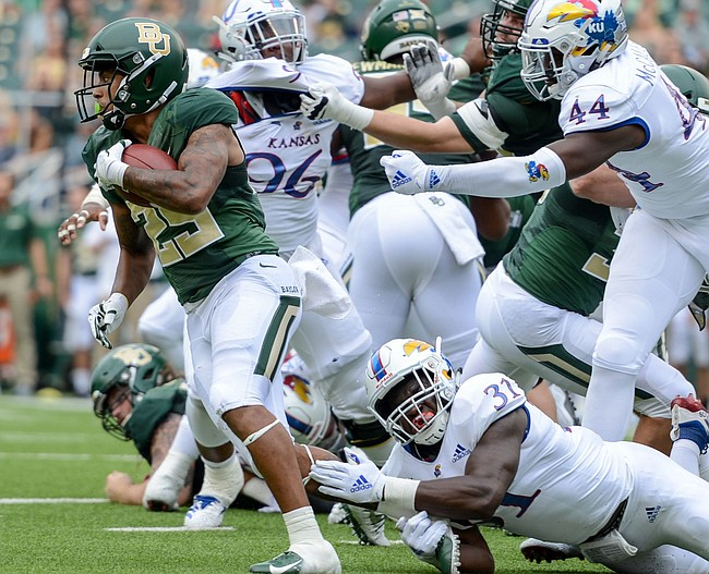 Kansas linebacker Osaze Ogbebor (31) trips down Baylor running back Trestan Ebner (25) during the first half of an NCAA college football game, Saturday, Sept. 22, 2018, in Waco, Texas.