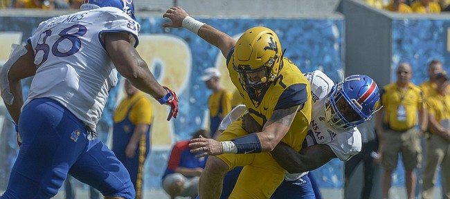 West Virginia quarterback Will Grier (7) fumbles the ball against Kansas during the second half of an NCAA college football game in Morgantown, W. Va., Saturday Oct. 6, 2018. (Craig Hudson/Charleston Gazette-Mail via AP)