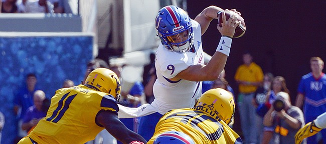Kansas quarterback Carter Stanley (9) is tackled by West Virginia linebackers David Long Jr. (11) and Kenny Bigelow, Jr. during the first half of an NCAA college football game against Kansas in Morgantown, W. Va., Saturday Oct. 6, 2018. (Craig Hudson/Charleston Gazette-Mail via AP)