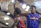 Red Team guard Marcus Garrett dips under Blue Team center David McCormack for a bucket during a scrimmage on Wednesday, June 13, 2018, at the Horejsi Family Athletics Center.