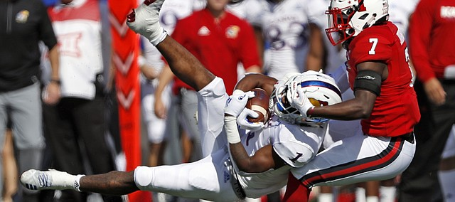 Texas Tech's Jah'Shawn Johnson (7) tackles Kansas' Pooka Williams Jr. (1) during the first half of an NCAA college football game Saturday, Oct. 20, 2018, in Lubbock, Texas.