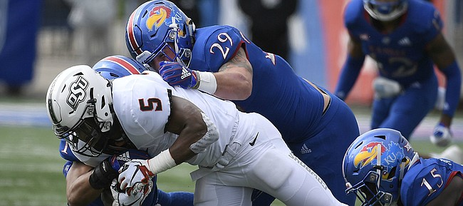 Kansas linebacker Joe Dineen Jr. (29) and safety Bryce Torneden take down Oklahoma State's Justice Hill on Saturday, Sept. 29, 2018.