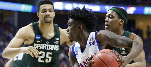 Kansas guard Lagerald Vick (2) drives to the bucket past Michigan State guard Cassius Winston (5) and Michigan State forward Kenny Goins (25) during the second half on Sunday, March 19, 2017 at BOK Center in Tulsa, Okla.