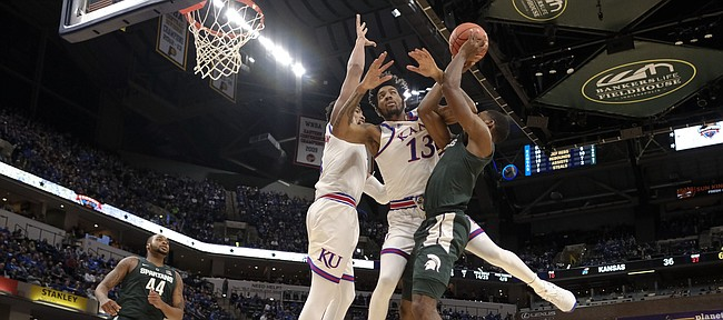 Kansas guard K.J. Lawson, center, fouls Michigan State forward Aaron Henry, right, during the first half of an NCAA college basketball game at the Champions Classic on Tuesday, Nov. 6, 2018, in Indianapolis. Kansas won, 92-87.