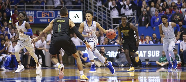 Kansas guard Devon Dotson (11) drives the ball up the court against Vermont guard Skyler Nash (1) during the first half, Monday, Nov. 12, 2018 at Allen Fieldhouse.