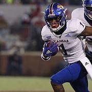 Kansas running back Pooka Williams Jr. (1) runs ahead of Oklahoma defenders during the first half of an NCAA college football game in Norman, Okla., Saturday, Nov. 17, 2018. (AP Photo/Alonzo Adams)
