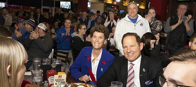 "Newly-hired Kansas head football coach Les Miles sits next to his wife, Kathy, as they listen to Kansas Athletic Director Jeff Long tell a story about hiring Miles during the ""Hawk Talk"" radio show on Sunday, Nov. 18, 2018, at Johnny's West in Lawrence. Miles was announced as the head coach earlier in the day."