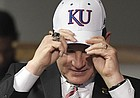 Newly hired University of Kansas football coach Les Miles puts on a KU hat during a press conference Sunday, Nov. 18, 2018, at Hadl Auditorium.
