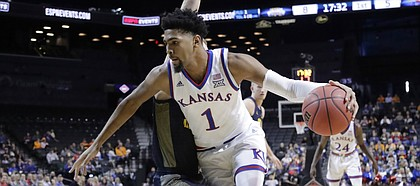 Kansas' Dedric Lawson (1) drives past Marquette's Joey Hauser (22) during the first half of an NCAA college basketball game in the NIT Season Tip-Off tournament Wednesday, Nov. 21, 2018, in New York.