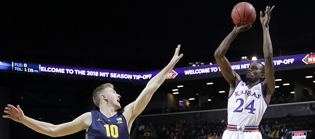 Kansas' Lagerald Vick (24) shoots over Marquette's Sam Hauser (10) during the first half of an NCAA college basketball game in the NIT Season Tip-Off tournament Wednesday, Nov. 21, 2018, in New York.