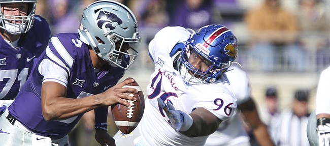 Kansas defensive tackle Daniel Wise (96) chases after Kansas State quarterback Alex Delton (5) during the first quarter on Saturday, Nov. 10, 2018 at Bill Snyder Family Stadium in Manhattan, Kan.