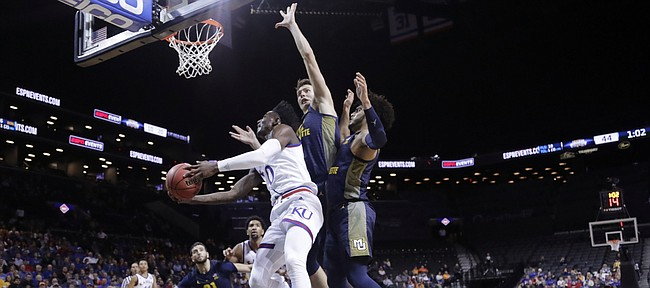 Kansas' Marcus Garrett (0) drives past Marquette's Matt Heldt, center, and Markus Howard, right, during the first half of an NCAA college basketball game in the NIT Season Tip-Off tournament Wednesday, Nov. 21, 2018, in New York.