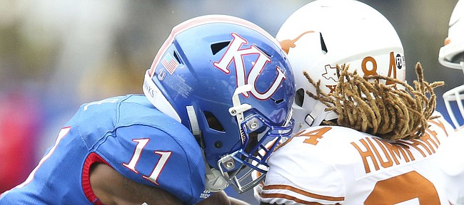 Kansas safety Mike Lee (11) and Kansas safety Bryce Torneden (1) put a hit on Texas wide receiver Lil'Jordan Humphrey (84) after a catch during the first quarter on Friday, Nov. 23, 2018 at Memorial Stadium.