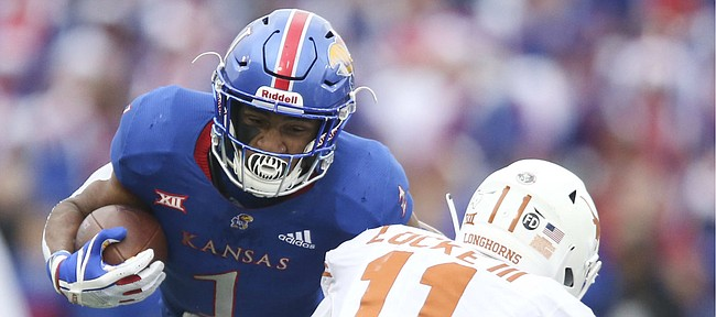 Kansas running back Pooka Williams Jr. (1) runs the ball against Texas defensive back P.J. Locke III (11) during the second quarter on Friday, Nov. 23, 2018 at Memorial Stadium.