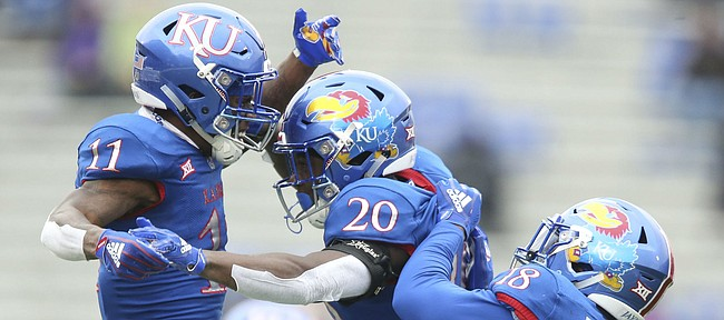 Kansas safety Emmanuel Moore (20) celebrates a hit on a Texas return man with Kansas safety Mike Lee (11) and Kansas linebacker Denzel Feaster (18) during the second quarter on Friday, Nov. 23, 2018 at Memorial Stadium.