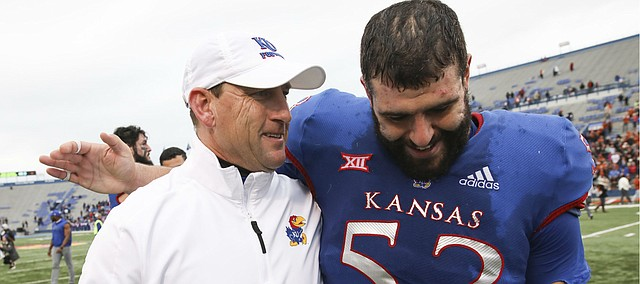 Kansas offensive lineman Alex Fontana (53) puts his arm around Kansas head coach David Beaty as Beaty leaves the field for his final time as head coach following Friday's 24-17 loss to Texas at Memorial Stadium.