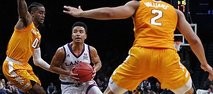 Kansas guard Devon Dotson drives to the basket between Tennessee's Jordan Bone (0) and Grant Williams (2) during the first half of an NCAA college basketball game in the NIT Season Tip-Off tournament Friday, Nov. 23, 2018, in New York. Kansas defeated Tennessee 87-81 in overtime. (AP Photo/Adam Hunger)