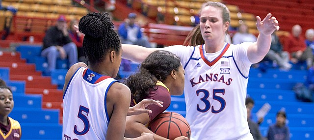 Iona's Gabrielle Joseph (21) is protecting the ball from a rebound as Kansas guard Aniya Thomas (5) and center Bailey Helgren (35) sets a trap to try to force a turnover in the first quarter on Sunday, Nov. 25, 2018 at Allen Fieldhouse.