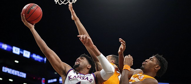 Kansas forward Dedric Lawson (1) drives to the basket past Tennessee guard Jordan Bowden, right, and another defender during the first half of an NCAA college basketball game in the NIT Season Tip-Off tournament Friday, Nov. 23, 2018, in New York. Tennessee 87-81 in overtime. (AP Photo/Adam Hunger)