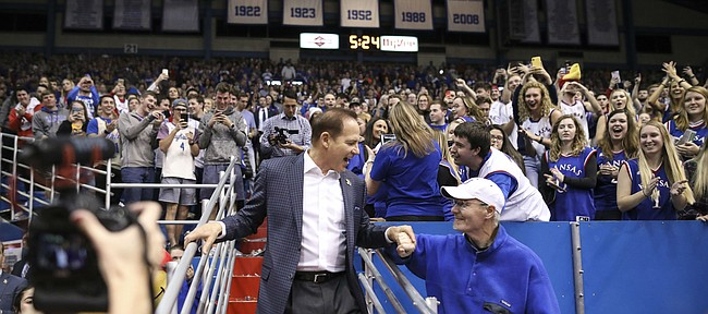 Newly-hired Kansas football coach Les Miles shakes hands with a fan as he is introduced to the Allen Fieldhouse crowd during halftime of the Jayhawks' game against Stanford.
