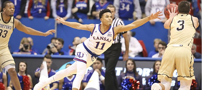 Kansas guard Devon Dotson (11) reaches for a pass to Wofford guard Fletcher Magee (3) as he defends the perimeter during the second half on Tuesday, Dec. 4, 2018 at Allen Fieldhouse.