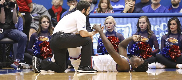 Kansas center Udoka Azubuike (35) lies on the ground with an injury as trainers come in to assist during the first half on Tuesday, Dec. 4, 2018 at Allen Fieldhouse.