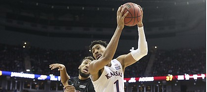 Kansas forward Dedric Lawson (1) turns to the bucket after catching the ball in the paint while defended by New Mexico State forward Johnny McCants (35) during the second half on Saturday, Dec. 8, 2018 at Sprint Center.