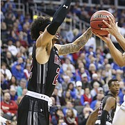 Kansas guard Devon Dotson (11) floats in for a shot between New Mexico State forward Eli Chuha (22) and New Mexico State forward Johnny McCants (35) during the first half on Saturday, Dec. 8, 2018 at Sprint Center.