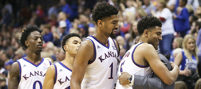 Kansas guard Quentin Grimes (5), Kansas forward Dedric Lawson (1) Kansas guard Devon Dotson (11) and Kansas guard Marcus Garrett (0) get hugs and congratulations from the bench as they check out of the game late in the second half on Tuesday, Dec. 4, 2018 at Allen Fieldhouse.