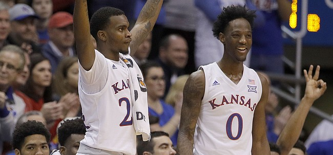 Kansas' Lagerald Vick, left, and Marcus Garrett (0) celebrate a teammate's basket during during the second half of an NCAA college basketball game against Eastern Michigan Saturday, Dec. 29, 2018, in Lawrence, Kan. Kansas won 87-63.