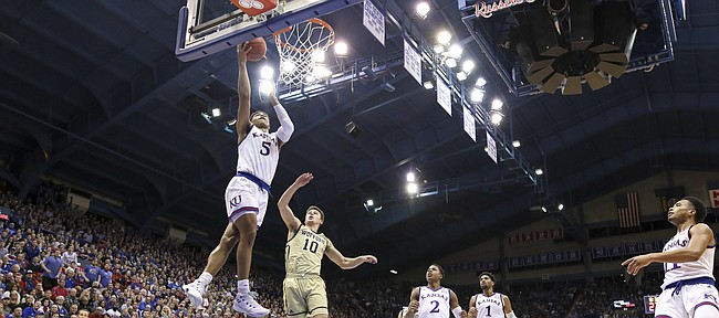Kansas guard Quentin Grimes (5) swoops in to the bucket past Wofford guard Nathan Hoover (10) for a bucket during the second half on Tuesday, Dec. 4, 2018 at Allen Fieldhouse.