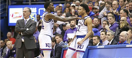Kansas guard Lagerald Vick (24) gives a celebratory shove to Kansas guard Devon Dotson (11) after Dotson's rejection of a TCU shot with seconds remaining in the game, Wednesday, Jan. 9, 2019 at Allen Fieldhouse. At left is TCU head coach Jamie Dixon.