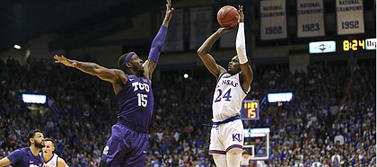 Kansas guard Lagerald Vick (24) puts up a three over TCU forward JD Miller (15) during the first half, Wednesday, Jan. 9, 2019 at Allen Fieldhouse.