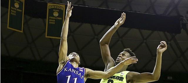 Kansas guard Devon Dotson (11) scores over Baylor forward Flo Thamba (0) in the first half of an NCAA college basketball game, Saturday, Jan. 12, 2019, in Waco, Texas.