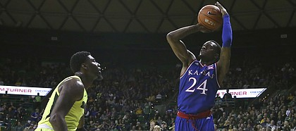 Kansas guard Lagerald Vick (24) shoots over Baylor guards Mark Vital (11) and Devonte Bandoo (2) in the second half of an NCAA college basketball game, Saturday, Jan. 12, 2019, in Waco, Texas. (AP Photo/Jerry Larson)
